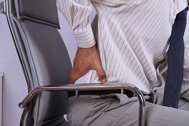 business man with back pain sitting in an office chair. - low section stock photos and pictures