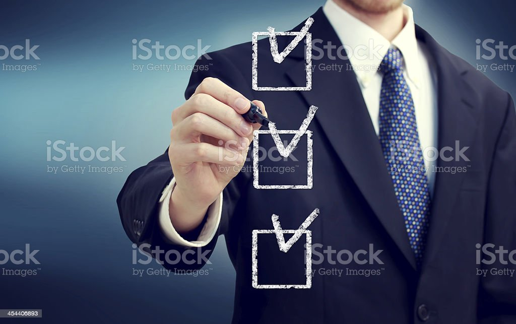 Business man with checkboxes Business man with check boxes over navy blue background Adult Stock Photo