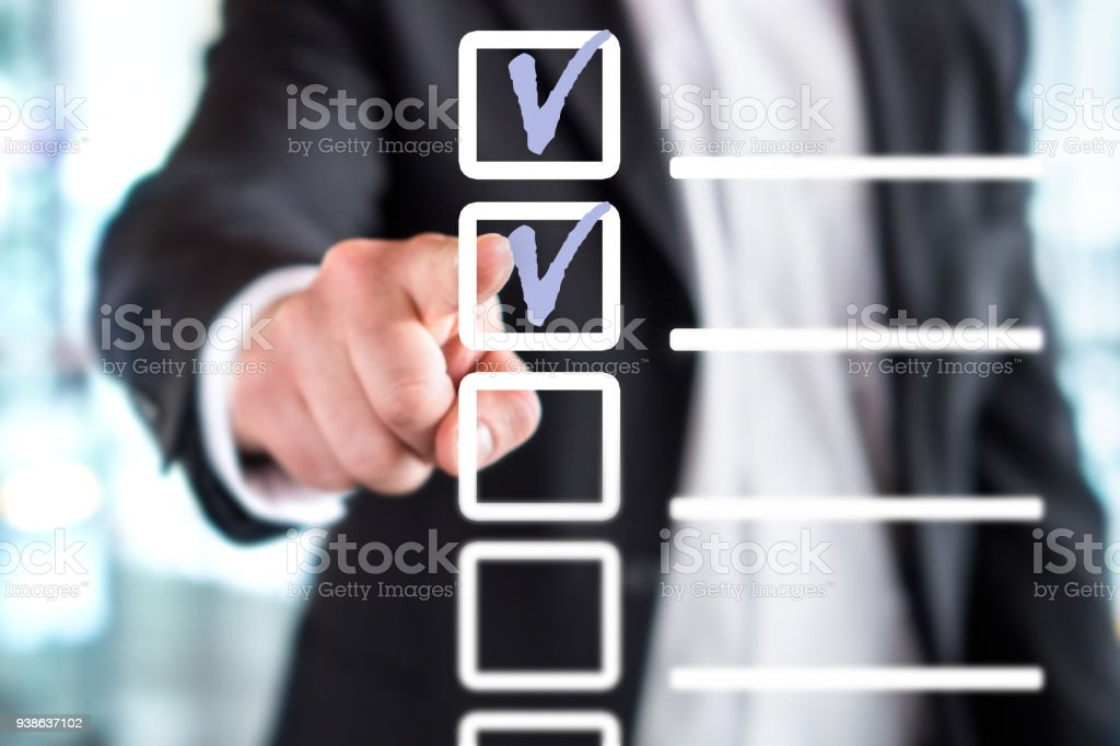 Business man with checklist and to do list. Man writing and drawing v sign check marks with hand and finger in square box. stock photo