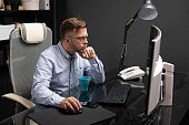 respectable man with bristles on his face in wrinkled shirt and jeans works in stylish office at computer. Businessman sitting at computer and in front of him is blue mug. entrepreneur propped his chin with his hand and works at computer