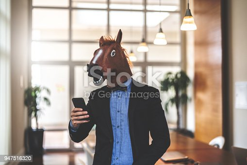 istock Business man with Horse Mask Using Mobile at Office 947516320