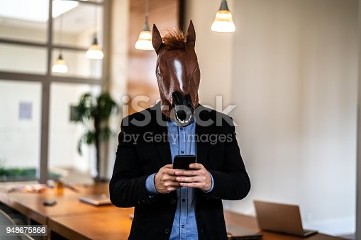istock Business man with Horse Mask Using Mobile at Office 948675866