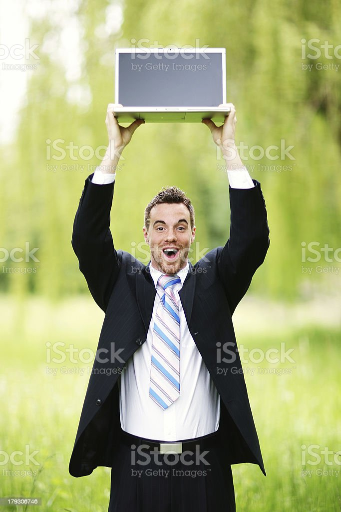 Business Man with Laptop Above Head in Nature royalty-free stock photo