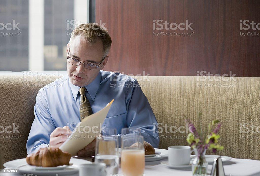Homme d'affaires avec des papiers dans un restaurant photo libre de droits