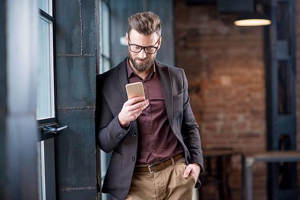 homme d'affaires avec le téléphone intelligent - mode bureau photos et images de collection