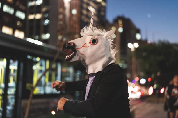 geschäftsmann mit einhorn maske tanzen in der stadt - heute ist freitag stock-fotos und bilder
