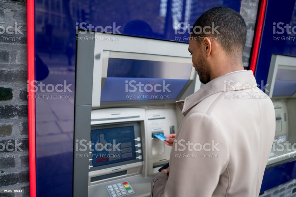 Business man withdrawing money from an ATM stock photo