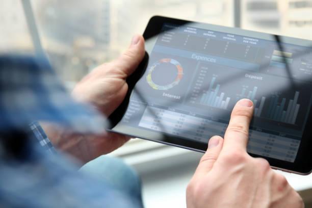 Geschäftsmann arbeiten und analysieren finanzielle Kennzahlen auf einen Graphen auf einem Tablet im Büro – Foto