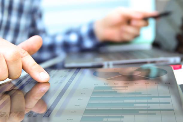 Geschäftsmann arbeitet und analysiert Finanzzahlen auf einem Graphen mit Laptop und Tablet – Foto