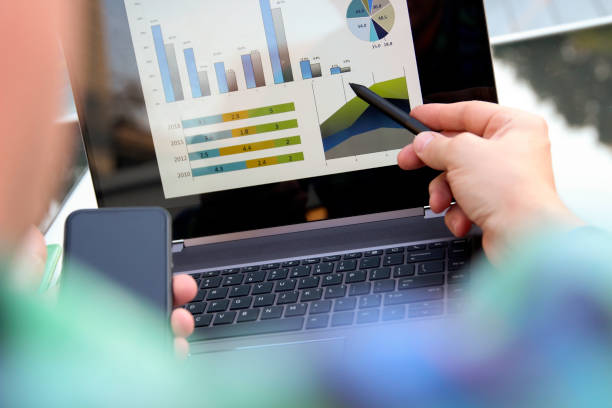 Business man working and analyzing financial figures on a graphs using laptop and tablet stock photo