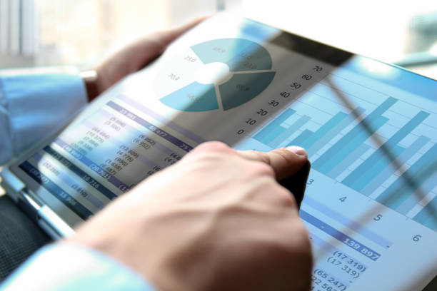 Business man working and analyzing financial figures on a graphs using laptop Business man working and analyzing financial figures on a graphs using laptop financial report stock pictures, royalty-free photos & images