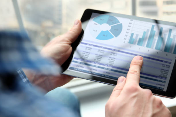 Business man working and analyzing financial figures on a graphs using laptop Business man working and analyzing financial figures on a graphs on a laptop in  the office financial report stock pictures, royalty-free photos & images