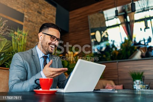 Photo of businessman using smartphone with earphones and laptop. Smiling business man sitting in restaurant listening to music. Happy man enjoying free wireless internet connection at coffee shop.