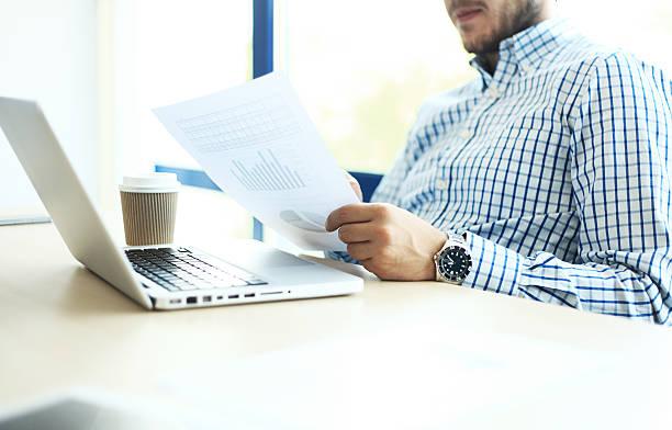 business man working at office with laptop and documents - lesen arbeitsblätter stock-fotos und bilder
