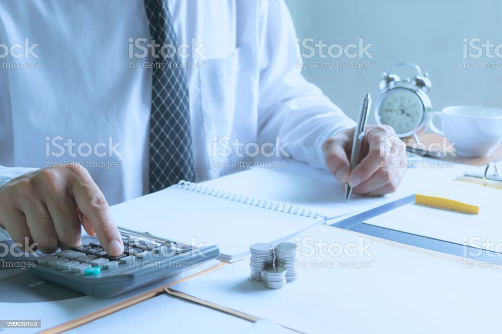 レポート プロジェクトとのための計算機を置くへの書き込みのオフィスで働くビジネスマンを保存、金融の概念、会計処理について計算します。 ストックフォト