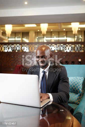 1053499704 istock photo Business man working late in hotel bar 179102457