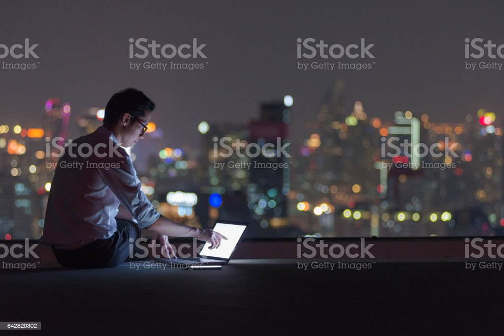 Business man working late with laptop computer on rooftop stock photo