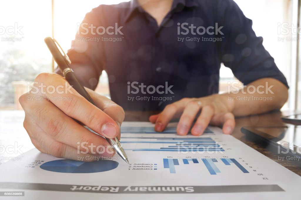 business man working with analysis graph chart document at office table - business and finance analysis concept stock photo