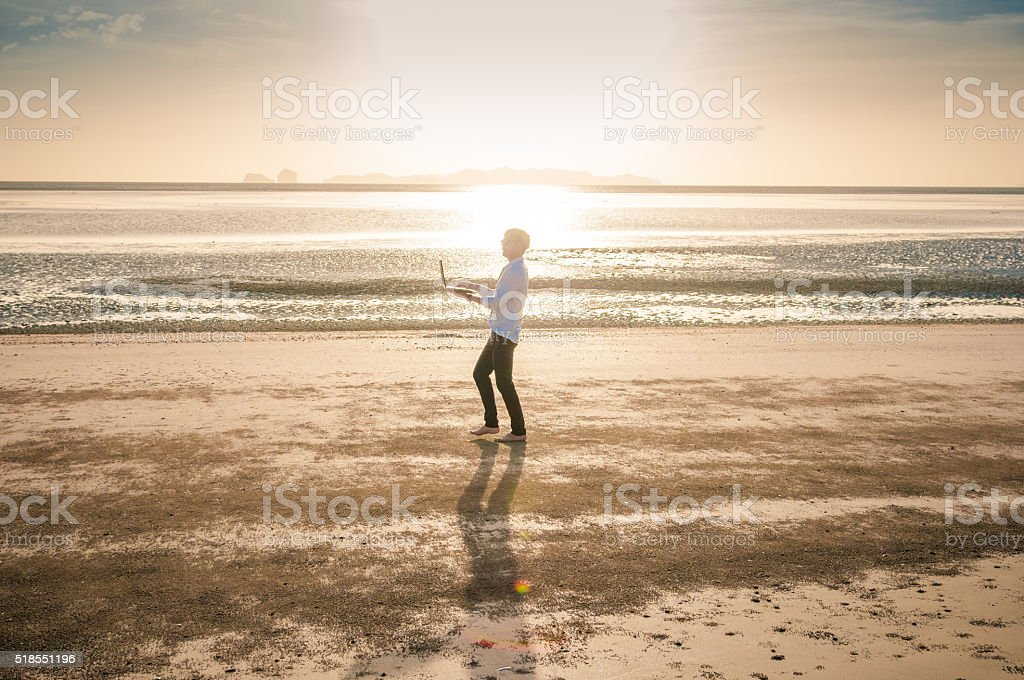 Business man working with laptop and smartphone beach background stock photo
