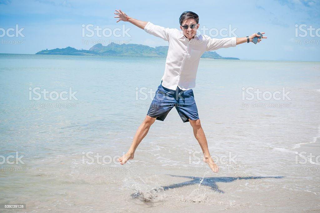 Hombre de negocios con ordenador portátil y teléfono inteligente playa de fondo foto de stock libre de derechos