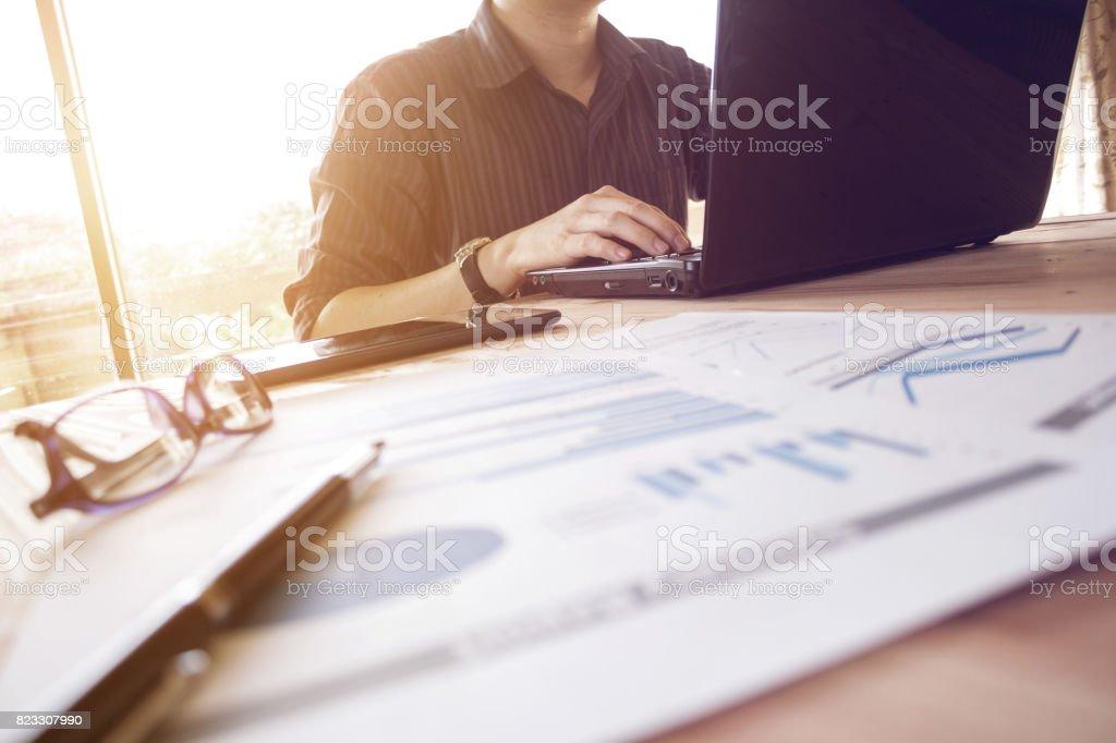 Geschäftsmann, arbeiten mit Laptop Computer, Handy und Analyse Graph Chart Dokument am Bürotisch – Foto
