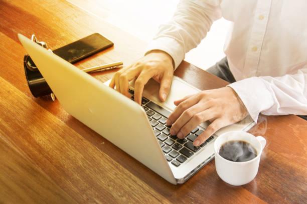 geschäftsmann, arbeiten mit laptop, dokumente und kaffee auf holztisch - lesen arbeitsblätter stock-fotos und bilder