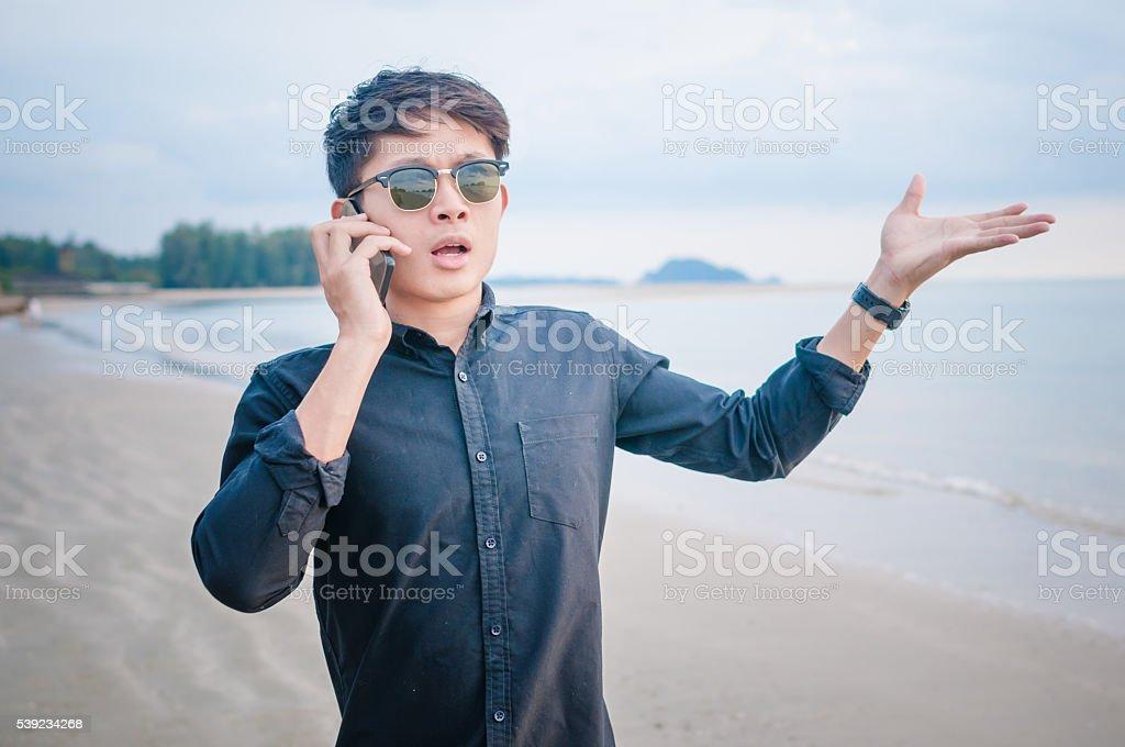 Hombre de negocios trabajando con teléfono inteligente playa de fondo foto de stock libre de derechos