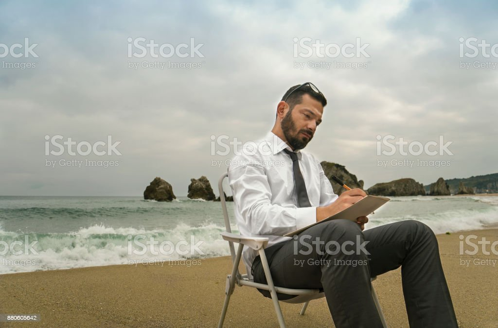 Business Man Writing Note in the Seaside While Sitting Down stock photo