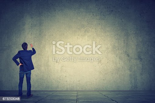 istock Business man writing on a large empty wall 673203048