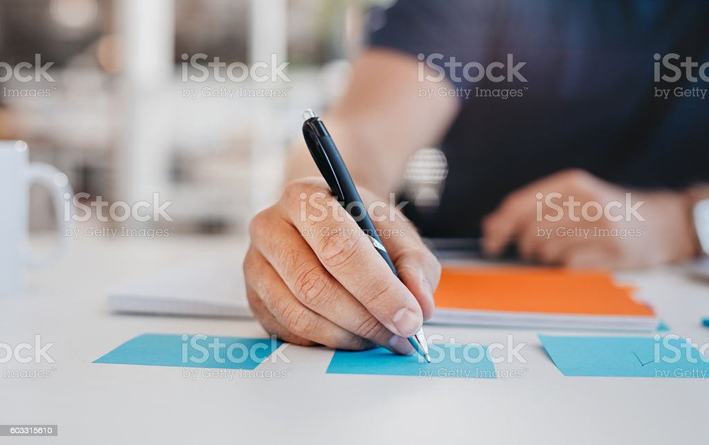 Business man writing on an adhesive note stock photo