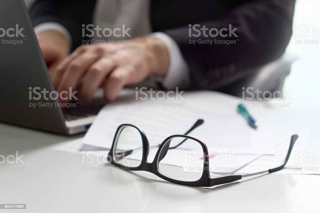 Business man writing with laptop in office with glasses on table. stock photo