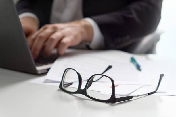 business-mann mit laptop im büro mit brille auf tabelle schreiben. - rechtsassistent stock-fotos und bilder