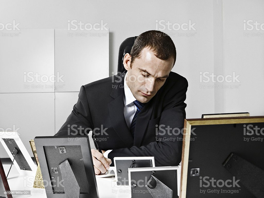 Business man writting, sitting behind desk with photo frames photo libre de droits
