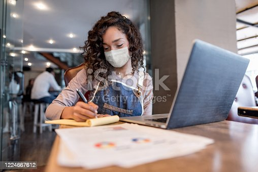 Business manager doing the books at a restaurant wearing a facemask to avoid coronavirus – pandemic lifestyle concepts