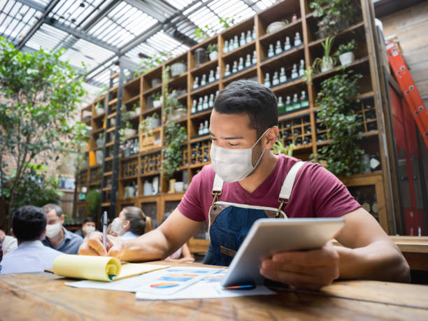 business manager doing the books at a restaurant wearing a facemask - small business owner stock pictures, royalty-free photos & images