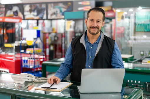 Portrait of a happy Latin American business manager working at a hardware store and looking at the camera smiling