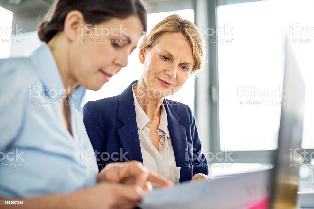 Business manager presenting financial data to her colleague stock photo