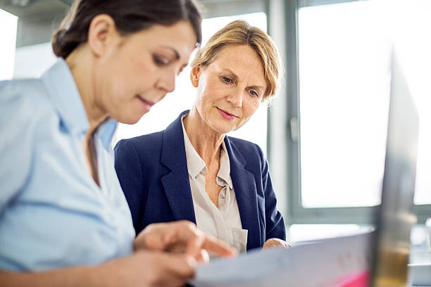 business manager presenting financial data to her colleague - directrice photos et images de collection