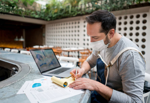 Business manager wearing a facemask while doing the books at a restaurant stock photo