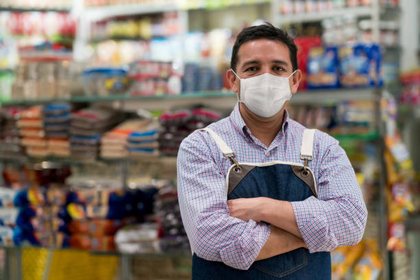 Business manager working at a convenience store wearing a facemask stock photo