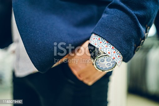 Young Caucasian businessman's hand in pocket wearing a watch.