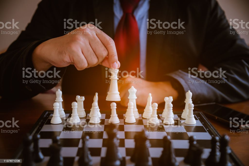 Business mans play chess board game. A white chess team and black...