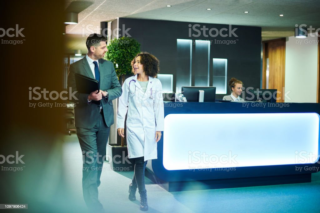 a businessman chats with a female doctor as they leave a boardroom...