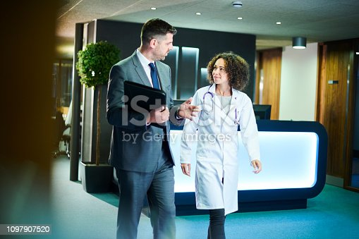 a businessman chats with a female doctor as they leave a boardroom meeting in a hospital