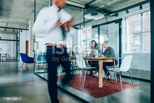 1163429625istockphoto Business meeting at busy corporate office. 1199100511