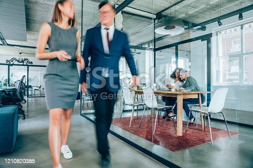 1163429625istockphoto Business meeting at busy corporate office. 1210820385
