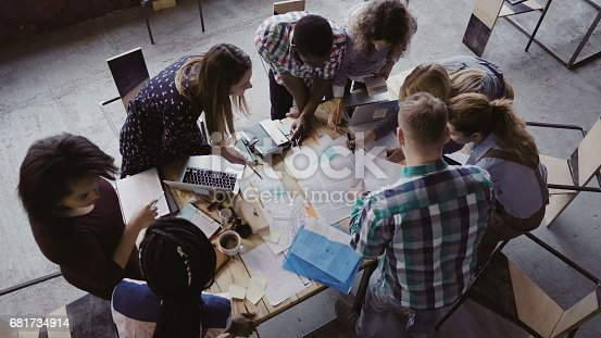 681735120istockphoto Business meeting at modern office. Top view of multiracial group of people working near the table together 681734914
