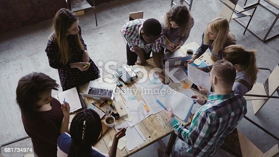 681735120istockphoto Business meeting at modern office. Top view of multiracial group of people working near the table together 681734974