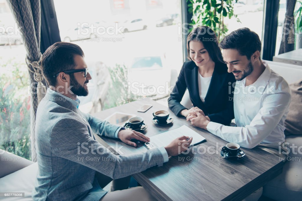 Business meeting at the cafe on a terrace. Joyful married couple is buying new apartment, young bearded attractive brunet lawyer in spectacles and suit is presenting contract to sign, they are having coffee - foto stock