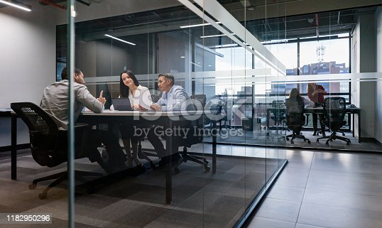 Group of workers in a business meeting at the office - shot through glass